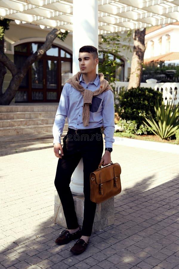 Hombre hermoso en equipo elegante con la presentación del bolso al aire libre fotografía de archivo libre de regalías