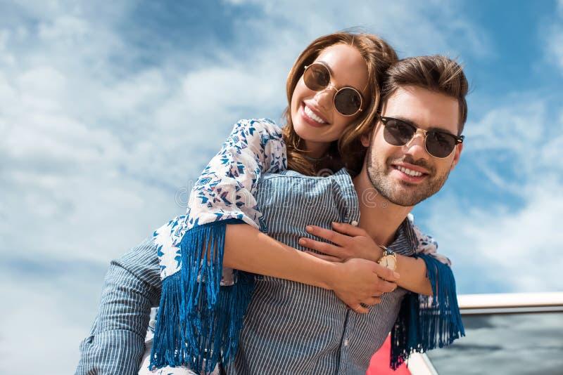 hombre hermoso en gafas de sol que lleva a cuestas a su novia sonriente foto de archivo