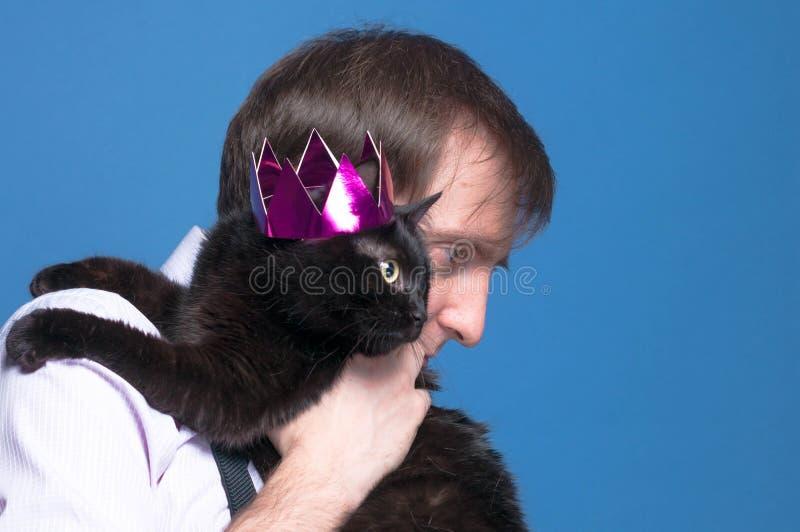 Hombre hermoso en la camisa que sostiene encendido el gato negro del hombro en corona brillante rosada en fondo azul fotografía de archivo
