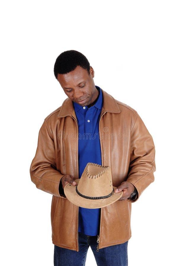 Hombre hermoso en la chaqueta de cuero marrón que sostiene sombrero imagen de archivo
