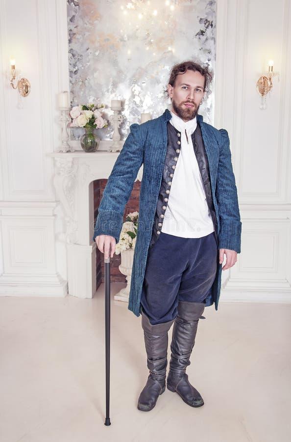 Hombre hermoso en la ropa medieval que se coloca en el cuarto fotos de archivo