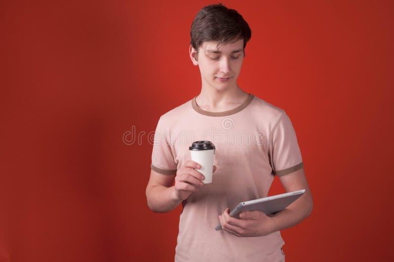 Hombre hermoso en la situación beige de la camiseta con la taza de papel y la mirada de la tableta digital imágenes de archivo libres de regalías