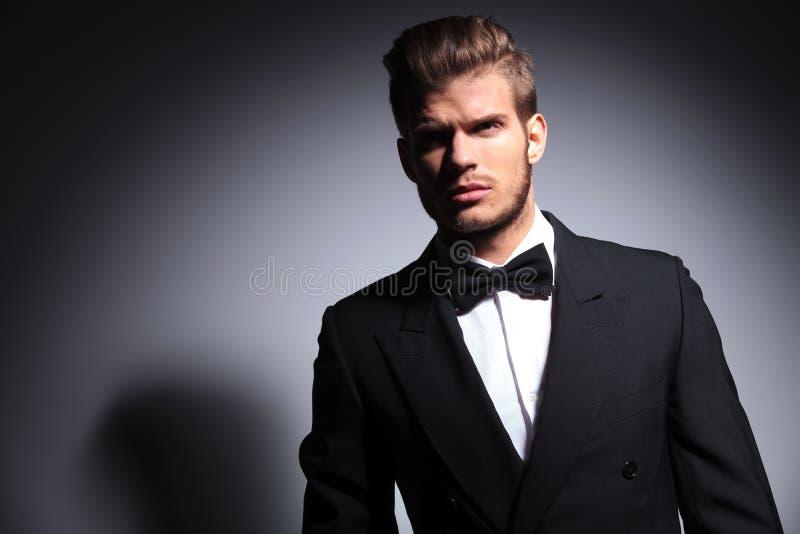 Hombre hermoso en smoking y corbata de lazo en una actitud dramática fotografía de archivo libre de regalías