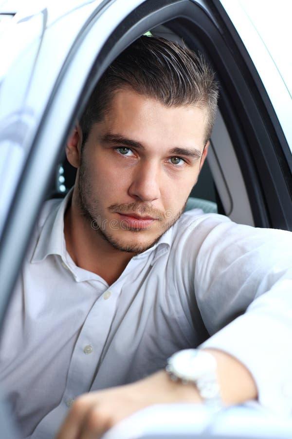 Hombre hermoso en su nuevos coche y sonrisa imagen de archivo libre de regalías