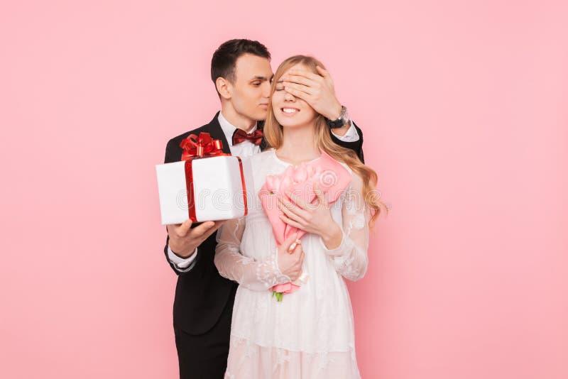 Hombre hermoso en un traje que hace una sorpresa a una mujer, cerrándose los ojos con sus manos en un fondo rosado, concepto del  fotografía de archivo libre de regalías