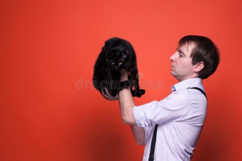 hombre hermoso erious en camisa con rodado encima de las mangas que se sostienen en el gato negro lindo de los brazos extendidos  fotos de archivo libres de regalías