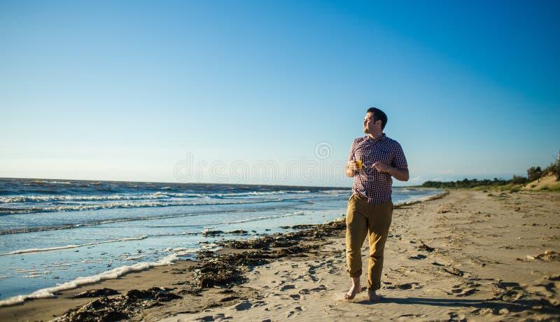 Hombre hermoso feliz que sonríe delante del océano con el vidrio de jugo de la fruta cítrica, ropa ligera cómoda que lleva fotografía de archivo