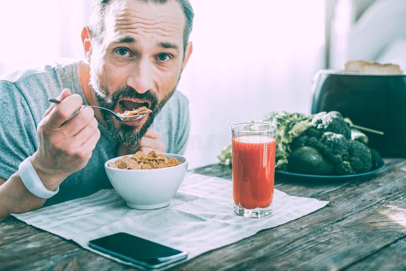 Hombre hermoso hambriento que desayuna en casa foto de archivo