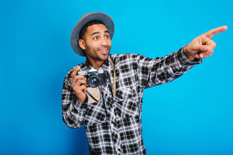 Hombre hermoso joven asombroso que se divierte con la cámara en fondo azul El viajar, disfrutando de días de fiesta, turismo, map fotos de archivo