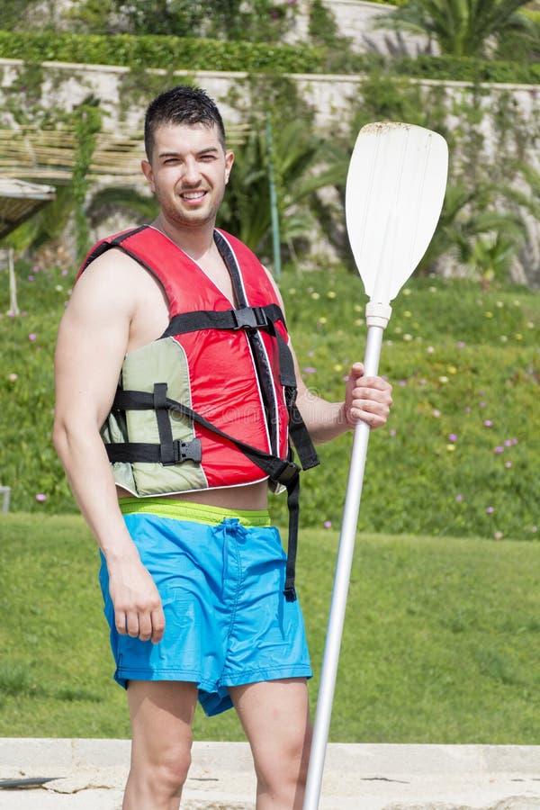 Hombre hermoso joven con el chaleco inflable que va a kayaking imagen de archivo libre de regalías