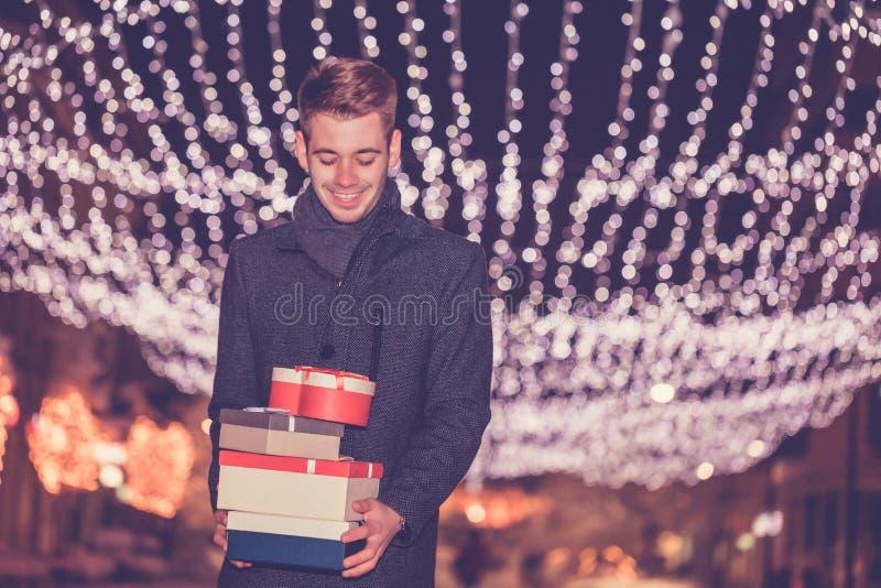 Hombre hermoso joven con el regalo de Navidad en la ciudad fotografía de archivo