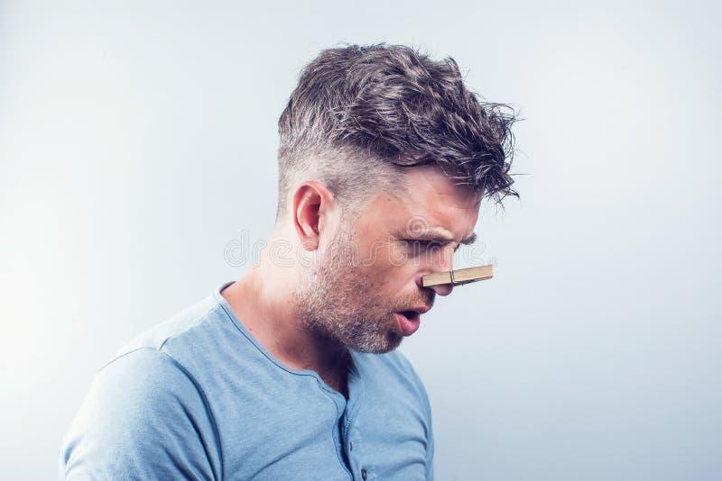 Hombre hermoso joven con la pinza en su nariz alergia fotografía de archivo libre de regalías