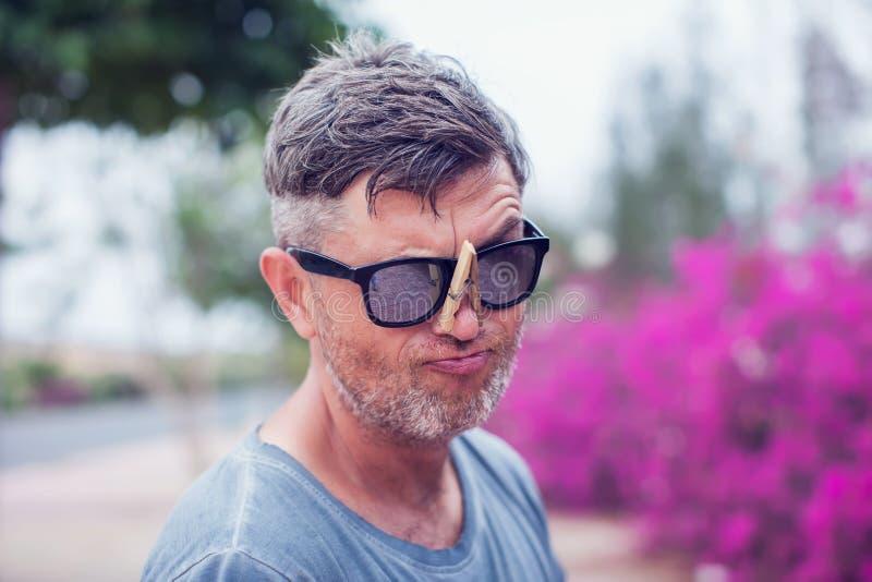 Hombre hermoso joven con la pinza en su nariz alergia imágenes de archivo libres de regalías