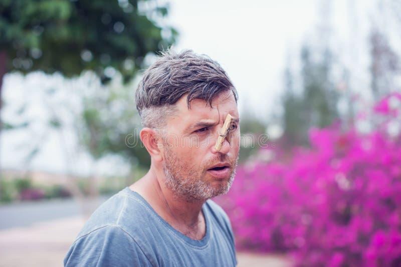 Hombre hermoso joven con la pinza en su nariz alergia imagenes de archivo