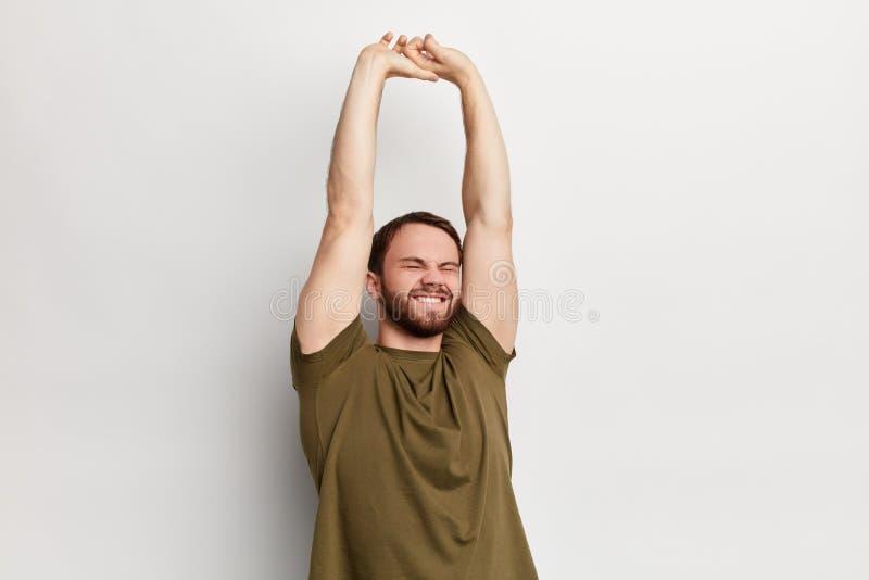 Hombre hermoso joven con los brazos aumentados que estiran detrás imagenes de archivo
