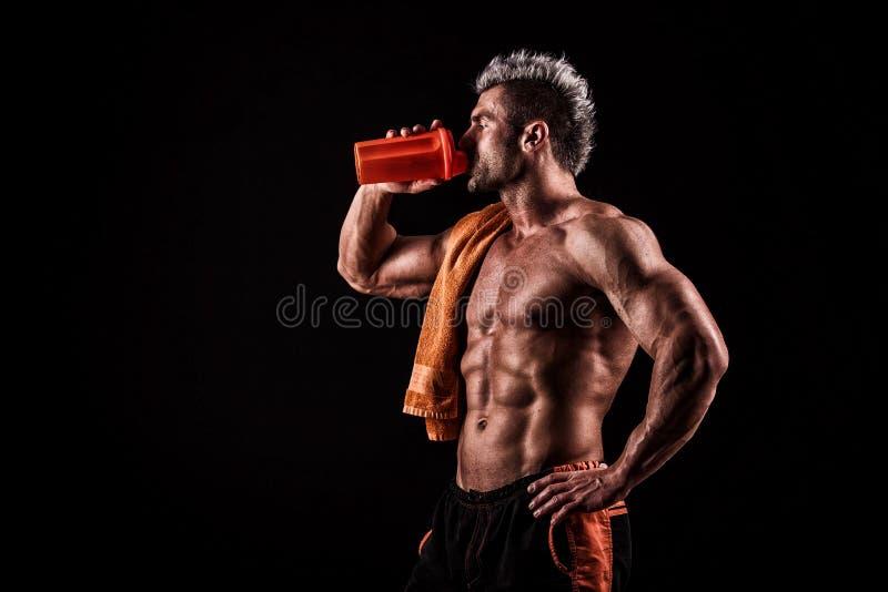 Hombre hermoso joven con los músculos fuertes, bebida de la proteína después del trai fotos de archivo libres de regalías