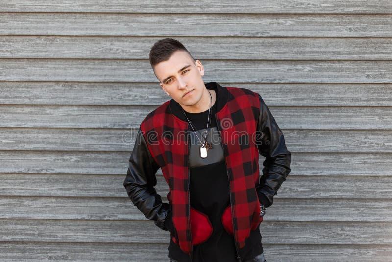 Hombre hermoso joven con un peinado elegante en una camiseta negra de moda en una chaqueta a cuadros roja elegante con las mangas foto de archivo