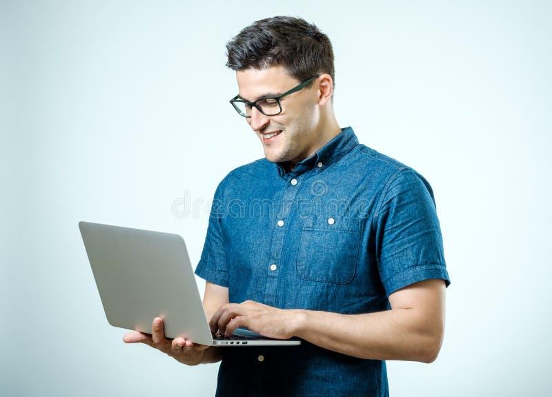 Hombre hermoso joven confiado en la camisa que sostiene el ordenador portátil fotos de archivo libres de regalías