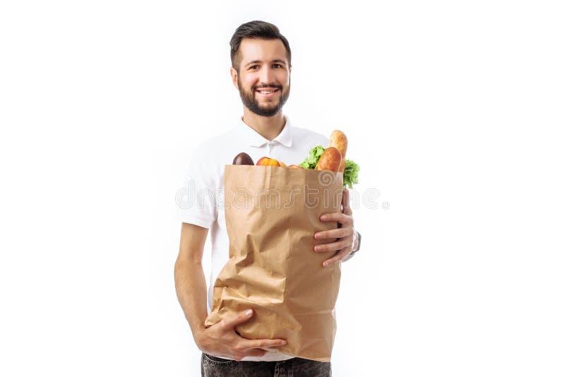 Hombre hermoso joven del inconformista que sostiene un bolso de la comida aislado en un w fotos de archivo libres de regalías