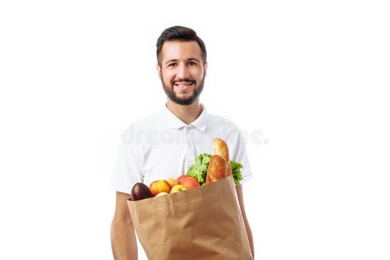 Hombre hermoso joven del inconformista que sostiene un bolso de la comida aislado en un w foto de archivo libre de regalías