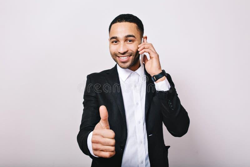 Hombre hermoso joven del retrato elegante en la camisa blanca, chaqueta negra sonriendo a la cámara, hablando en el teléfono en e fotografía de archivo libre de regalías