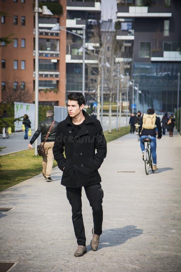 Hombre hermoso joven elegante en la capa negra que se coloca en centro de ciudad fotos de archivo libres de regalías
