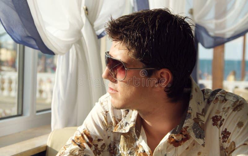 Hombre hermoso joven elegante en las gafas de sol que miran la ventana imagen de archivo