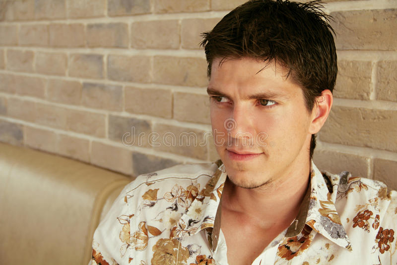 Hombre hermoso joven elegante que mira lejos en fondo de la pared de ladrillo foto de archivo