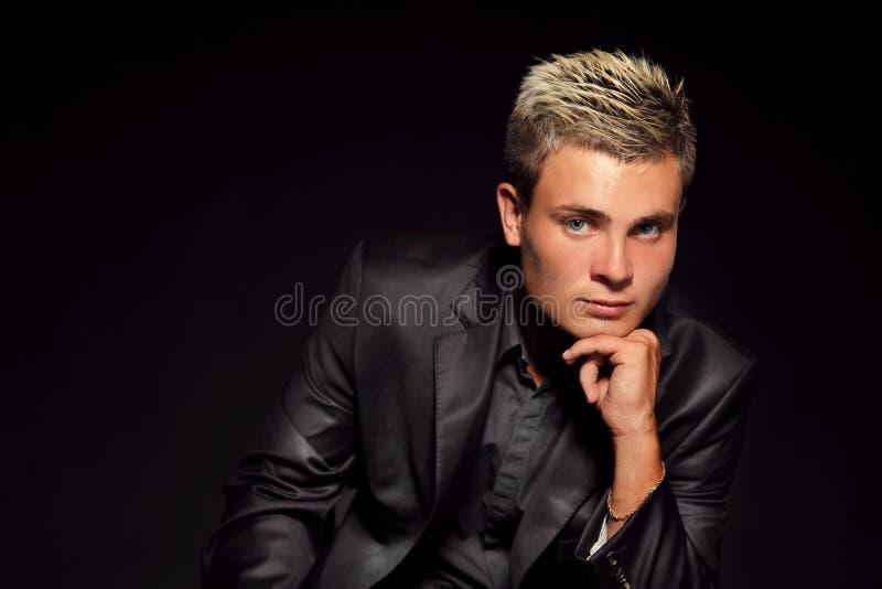 Hombre hermoso joven elegante sobre oscuridad. Retrato de la moda del estudio. imágenes de archivo libres de regalías