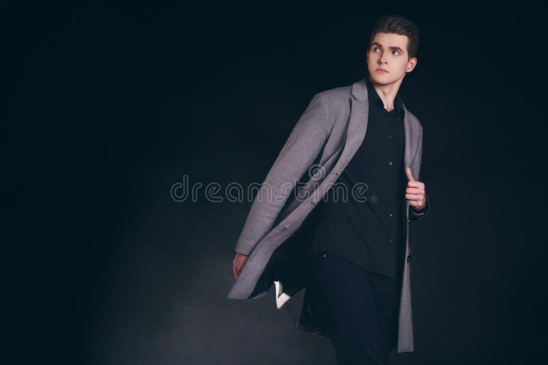 Hombre hermoso joven en capa Retrato del hombre bien vestido de moda que presenta en capa elegante gris Muchacho confiado y enfoc imágenes de archivo libres de regalías