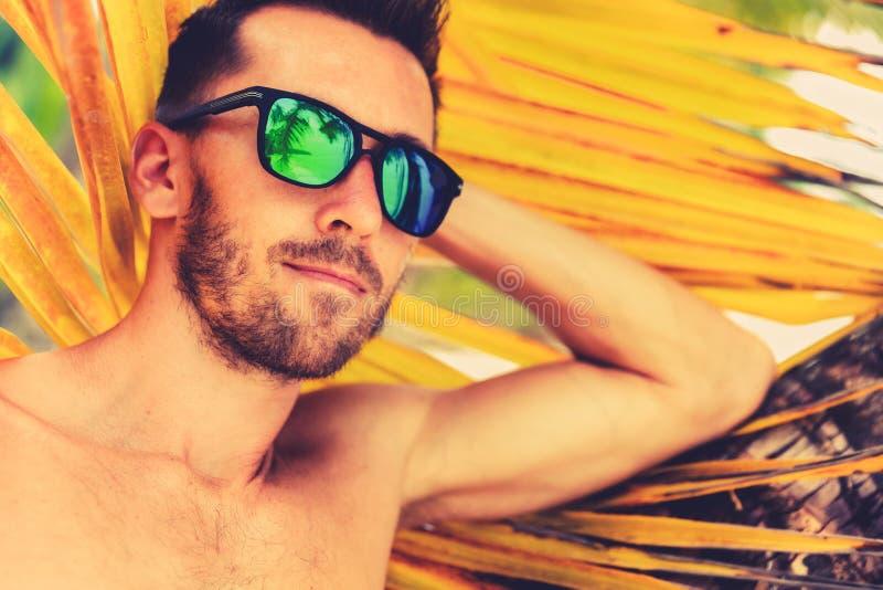 Hombre hermoso joven en gafas de sol en la playa imágenes de archivo libres de regalías