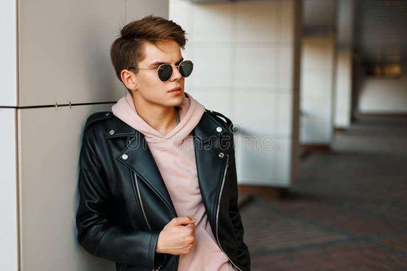 Hombre hermoso joven en gafas de sol tipo aviador en un enchufe de cuero negro foto de archivo libre de regalías
