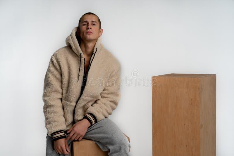 Hombre hermoso joven en la ropa de deportes elegante que se sienta en el cubo de madera, mirando la c?mara aislada sobre el fondo fotos de archivo libres de regalías