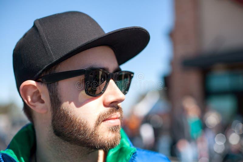 Hombre hermoso joven en las lentes de sol negros que miran la calle en día de verano fotos de archivo