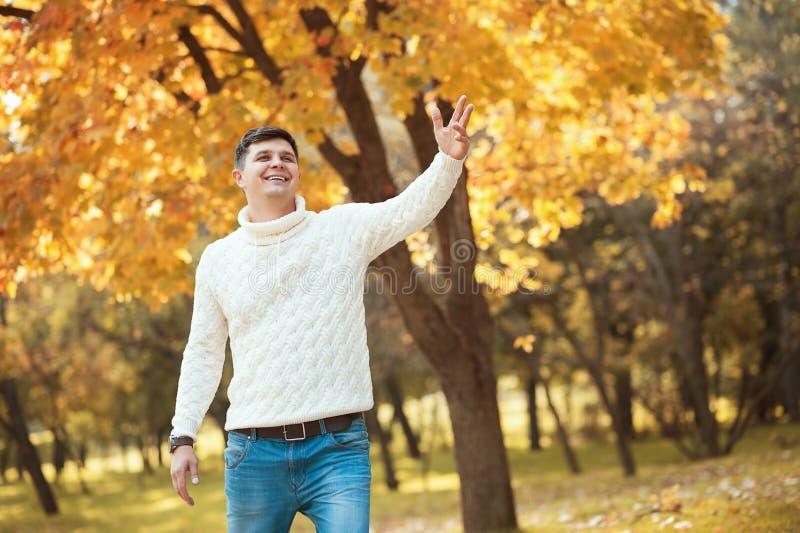 Hombre hermoso joven en suéter y vaqueros que permanecen en parque anaranjado del otoño que sonríen y que agitan alguien fotografía de archivo