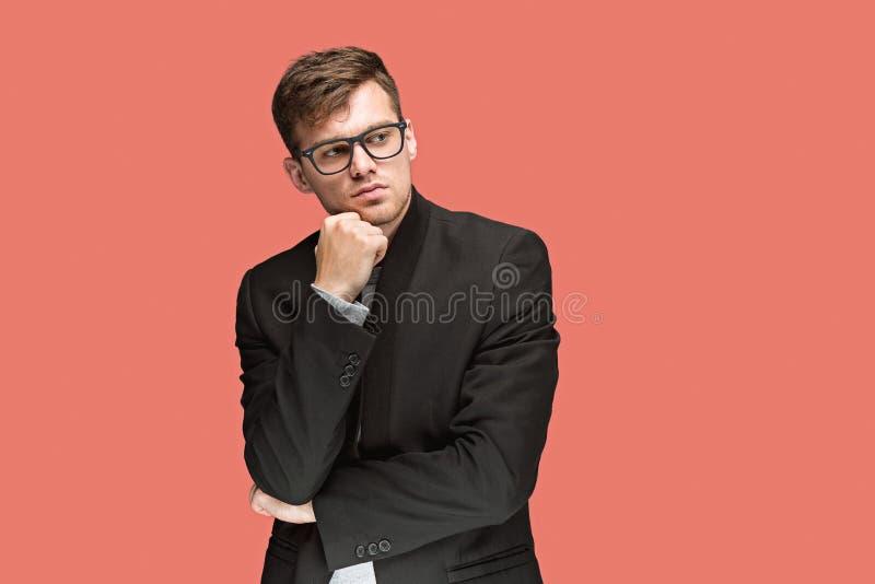 Hombre hermoso joven en traje negro y los vidrios aislados en fondo rojo imagen de archivo libre de regalías