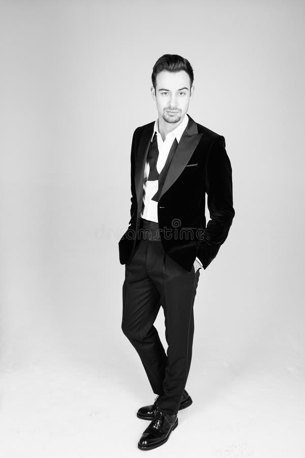 Hombre hermoso joven en un traje, la situación y la mirada de la cámara fotografía de archivo
