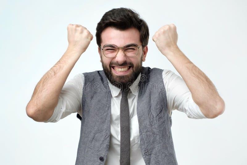 Hombre hermoso joven feliz que gesticula como él tiene tener éxito en su proyecto del trabajo imagenes de archivo