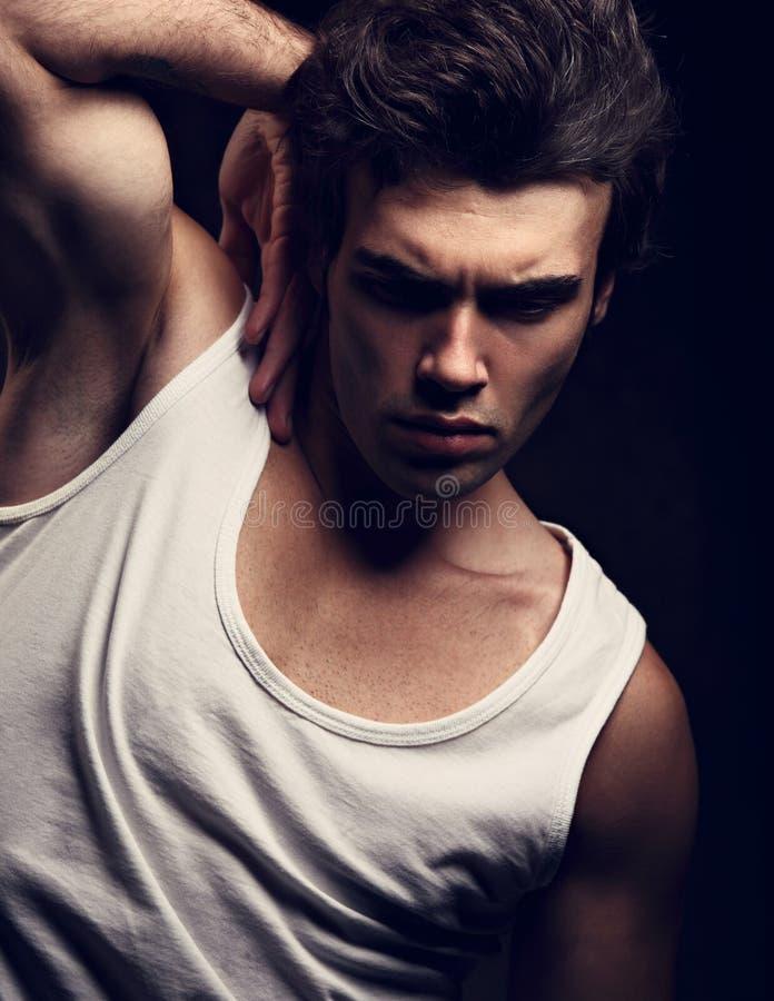 Hombre hermoso joven fuerte atractivo que presenta en la camiseta blanca en el drak s fotos de archivo libres de regalías