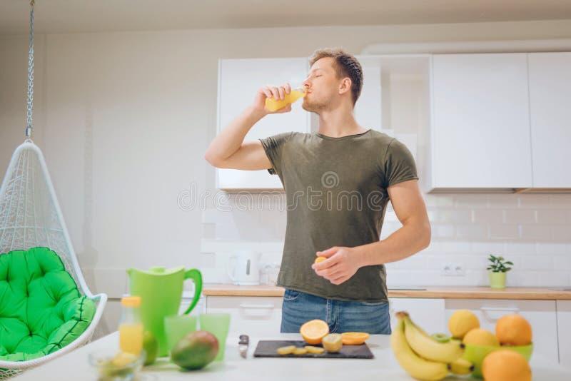 Hombre hermoso joven que bebe el zumo de naranja fresco en la cocina Alimento sano Comida vegetariana Detox de la dieta imagenes de archivo