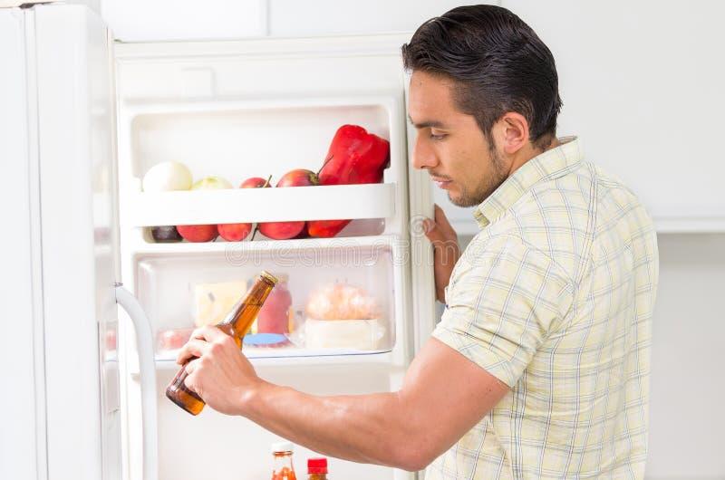 Hombre hermoso joven que busca la comida en el refrigerador fotografía de archivo