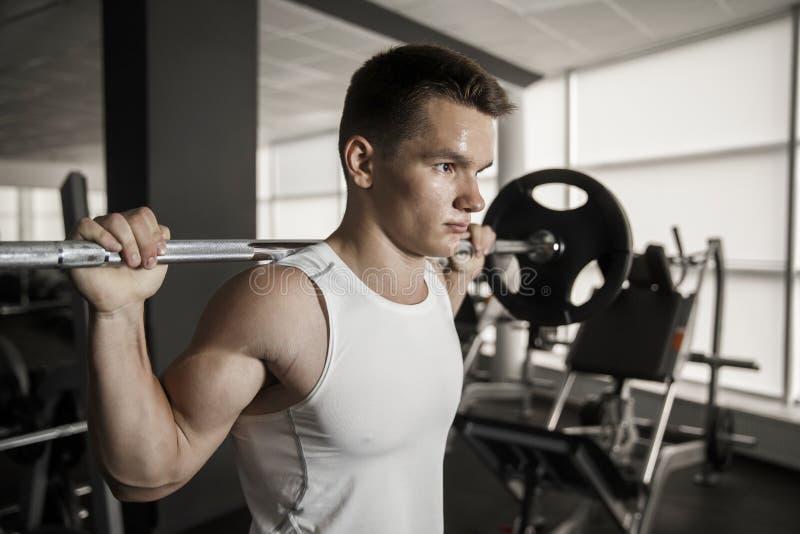 Hombre hermoso joven que ejercita con una posición en cuclillas del barbell en un gimnasio imagenes de archivo