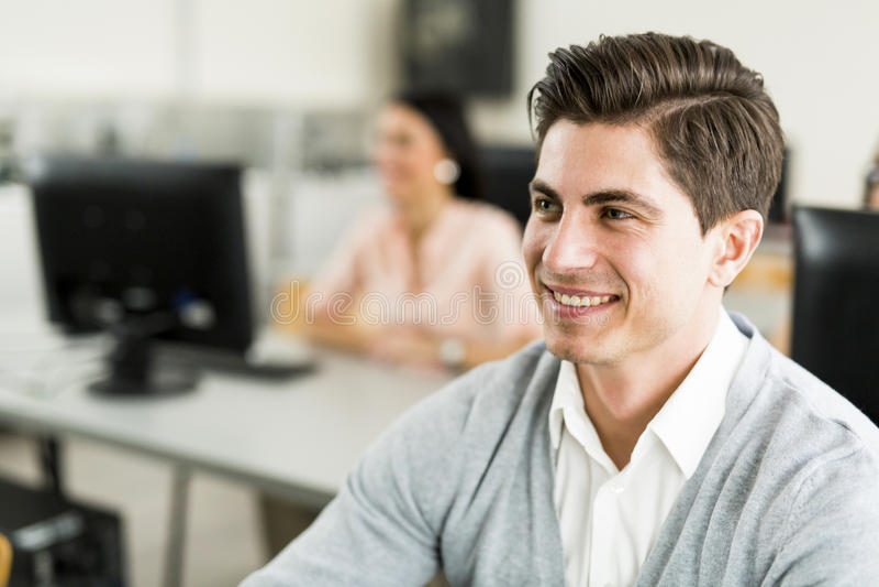 Hombre hermoso joven que estudia la tecnología de la información en un classroo imágenes de archivo libres de regalías
