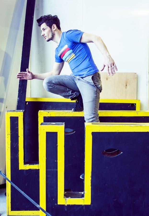 Hombre hermoso joven que hace el parkour en gimnasio dentro, concepto de la gente del deporte de la forma de vida imagenes de archivo