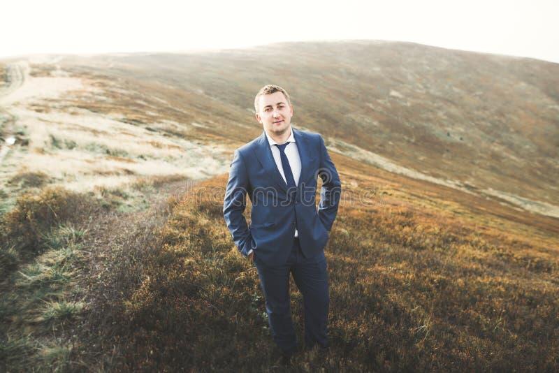 Hombre hermoso joven que presenta en la puesta del sol en la montaña imagen de archivo