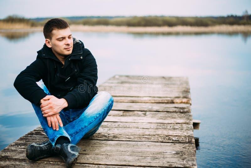 Hombre hermoso joven que se sienta en el embarcadero de madera, relajación, pensando, imagen de archivo libre de regalías