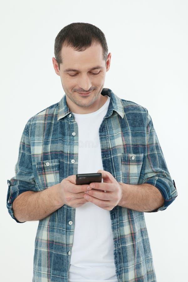 Hombre hermoso joven que usa smartphone en el fondo blanco Copie el SP fotografía de archivo libre de regalías