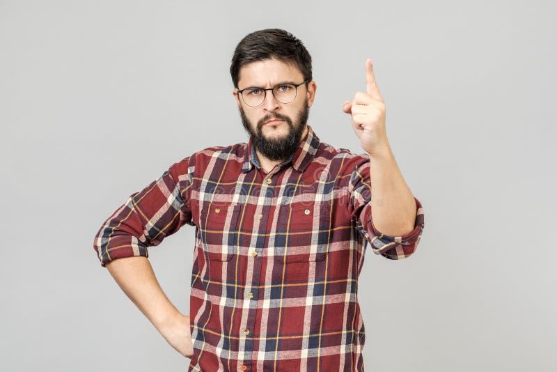 Hombre hermoso joven sobre fondo gris aislado que señala con el finger para arriba foto de archivo libre de regalías