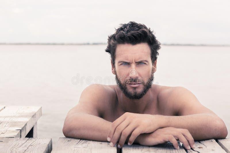 Hombre hermoso magnífico confiado sin la camisa en el mar fotografía de archivo libre de regalías
