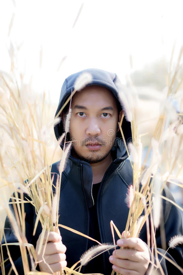 hombre hermoso misterioso en la sudadera con capucha negra que se coloca en la hierba fi fotografía de archivo libre de regalías